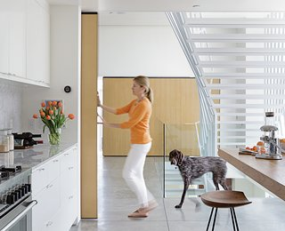 "A Minimalist Duplex in Venice, California - Photo 4 of 9 - A nine-foot-tall door covered with quarter-inch white oak slides along a ceiling rail and can be moved with just a finger to close off Don and Lisa's kitchen or bedroom. Made of wood and metal, and welded onsite, the door moves along 400-pound-capacity rollers by McMaster-Carr. A matching sliding door opposite hides a storage area. ""Because of their size, the doors had to be made inside,"" says Don, who did the job himself."