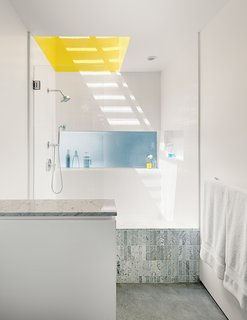 "A Minimalist Duplex in Venice, California - Photo 8 of 9 - The master bathroom has a small window and a large skylight above the shower—and shares a translucent glass expanse with the kitchen, where it becomes the backsplash. ""Even though it's a buried room,"" Don says, ""we have three sources of natural light. For the shower, we made a very high curb so you can stop up the drain and turn it into a big soaking tub. We used white, one-by-four-inch or one-by-six-inch Carrara marble tiles from Royal Stone and Tile. They come on a 12-by-12-inch sheet. I got the small tiles because you can use them to work the bottom plane into the shower."""