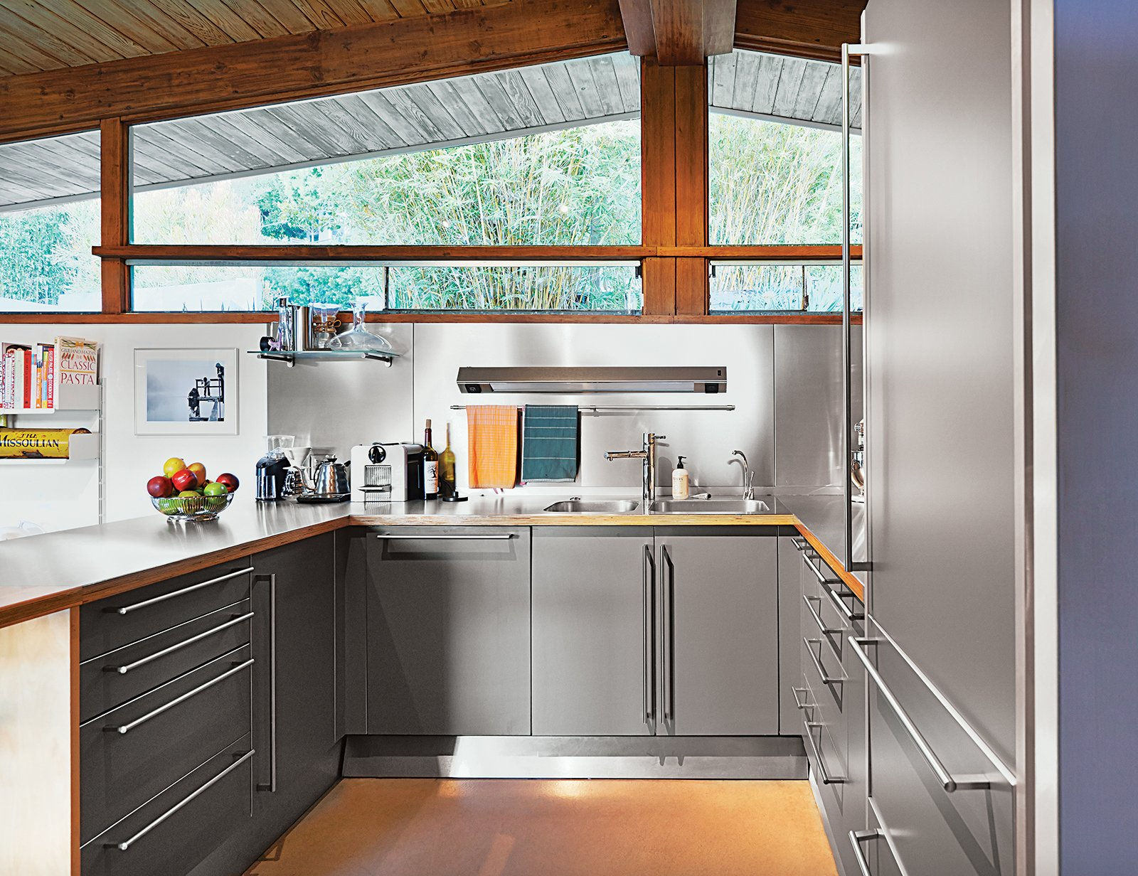 A previous owner remodeled the kitchen in 2000, outfitting it with stainless-steel cabinets by Bulthaup as well as a Sub-Zero refrigerator and an induction stove by Diva. Tagged: Kitchen and Metal Counter.  Midcentury Homes by Dwell from A Midcentury Home Keeps the History Alive