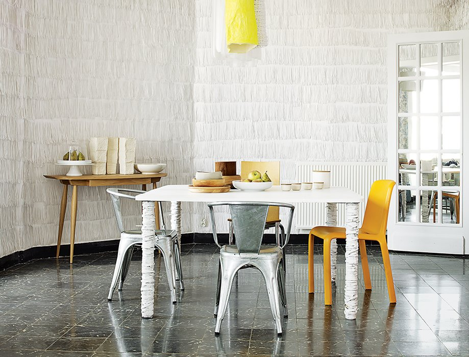 Pedrali's orange Frida 752 chair, two metal Tolix Marais chairs, and Philippe Starck's Olly Tango seat surround a dining table that resident Pierre Pozzi wrapped in paper.  Photo 10 of 10 in 10 Modern Renovations to Homes in Spain