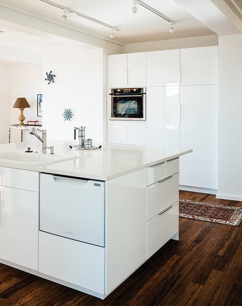 "The kitchen, which sits at the center of the house, features recycled glass countertops, Ikea cabinets, and carbonized bamboo floors. ""We had Thanksgiving dinner there,"" says the daughter. ""There's no sense of the house as small. It feels like a house."""