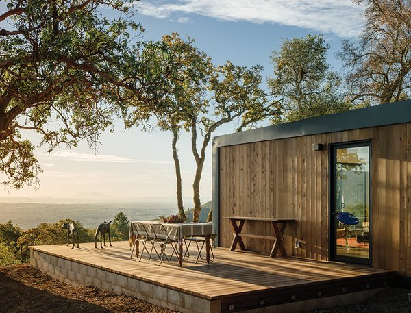 This Northern California Prefab Gets a Dose of Universal Design - Photo 6 of 8 - The deck offers views and a quiet spot for outdoor dining. The Western red cedar vertical siding is naturally resistant to rot and decay, making it a hardy choice for the exterior. The bronze wolf sculpture is by Sharon Loper.