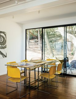"This Northern California Prefab Gets a Dose of Universal Design - Photo 7 of 8 - David Rowland stacking chairs join a 1970s Italian glass-and-steel table in the dining room. The daughter loves being able to stop in to visit. ""I'm over there ten times a day. It's brought me such peace."""