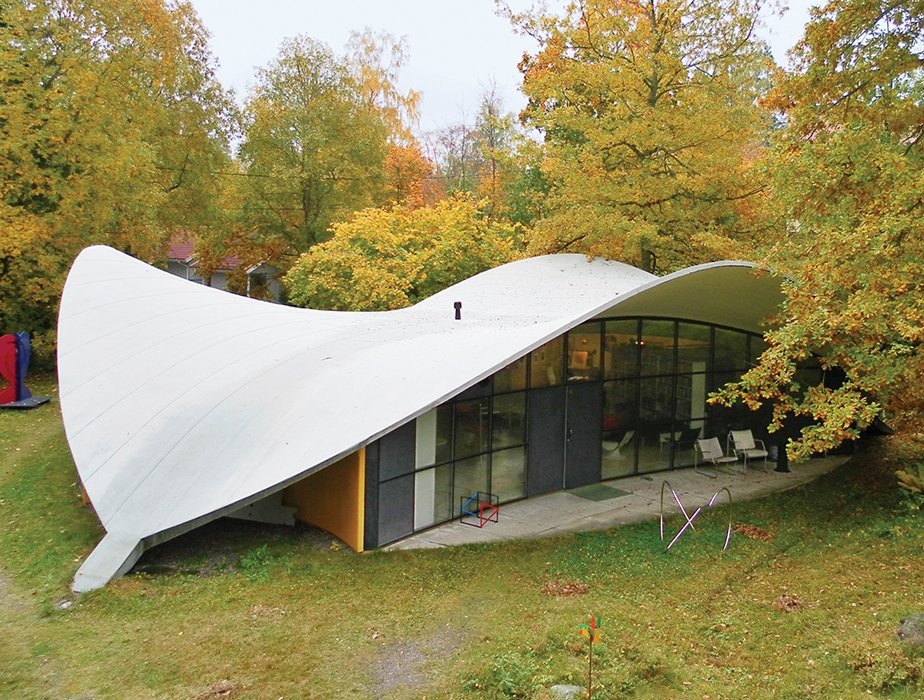 "The 1968 house's shape—a rounded triangle topped with a sweeping concrete roofline that suggests a helmet as it rises above huge banks of windows—lends itself totally to Kukkapuro's philosophy. ""It is a structure in waiting, prone to change as the landscape around it—not yet a form, rather a possibility,"" he says. ""It changes in harmony with the seasons and the moods of its inhabitants."" Tagged: Outdoor, Trees, Grass, Back Yard, Concrete Patio, Porch, Deck, and Small Patio, Porch, Deck.  Photo 2 of 7 in Modern Studio of a Finnish Design Legend"