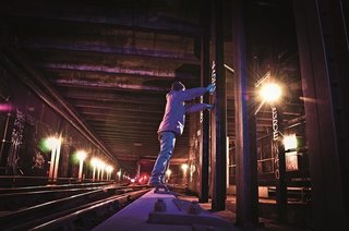 Graffiti artist standing on a wood covering over the third rail. Photo courtesy Jurne.