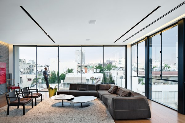 The living room features stunning views of the city, a Bend sofa and Phoenix coffee tables, both by Patricia Urquiola for B&B Italia and Moroso, respectively, and two Gray armchairs by Piero Lissoni for Living Divani.