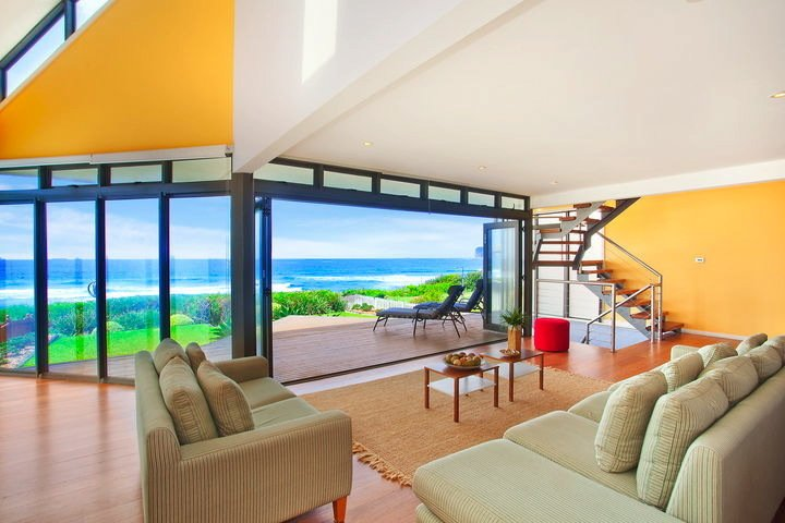 """Multi-Hued Beach Escape Near Sydney (North Avoca, Australia)  While this resort town rental is lit up with blocks of solid colors on the striking side of the Pantone scale, visitors will likely fixate on the shades of blue visible via the panoramic Pacific view. This coastal spot about 60 miles from Sydney also boasts a geometric roof and deck, further accentuating the ocean and sky awaiting outside.   Listing at """"Life is good...at the beach!"""""""