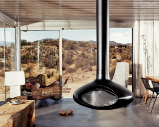 "A view from the interior of the ""iT House"" , the home is more a watchtower for the desert scenery. The large expanses of operable sliding glass doors offer plenty of cross-ventilation and the cool concrete floors  provide ample thermal mass."