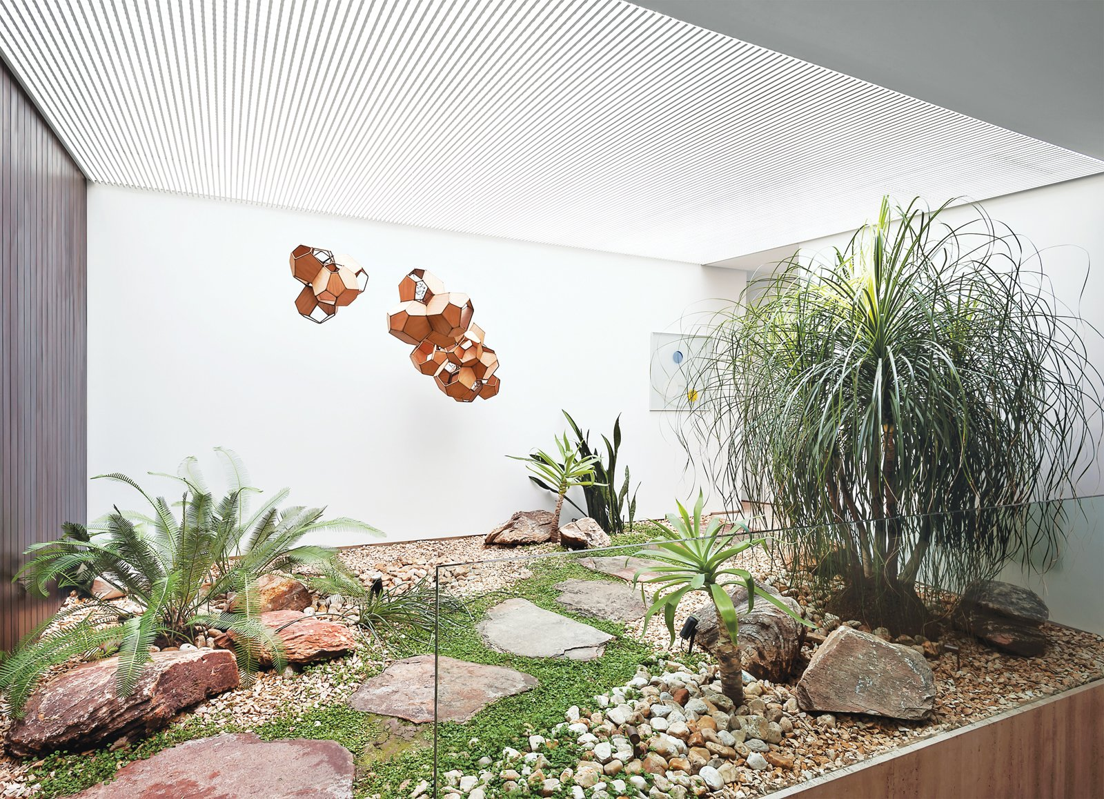 A small interior courtyard features a huge skylight and the sculpture Air-Port-City/Cloud-City/ 14-5-4 Cloud Modules 30 Net by Tomás Saraceno.  Impressive Indoor Gardens by Allie Weiss from Blockbuster Movies Can't Compete with These Monumental Views