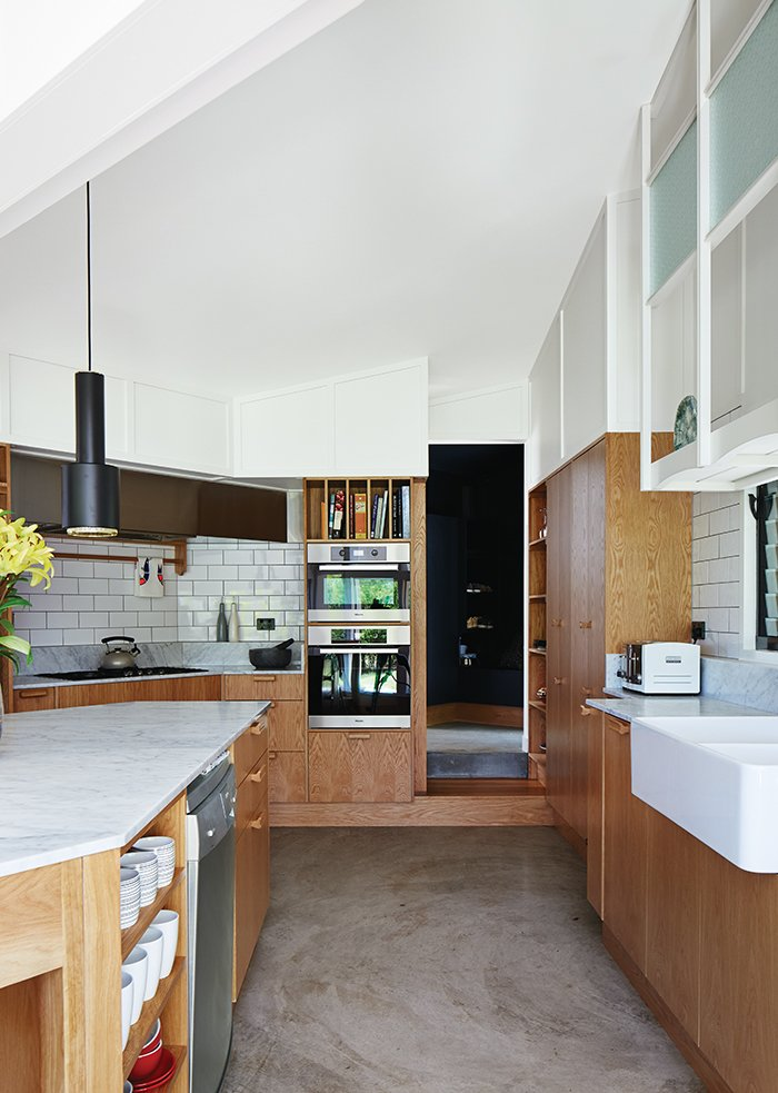 Brisbane-based studio Owen and Vokes and Peters designed a modern kitchen addition for a traditional Queensland-style timber house. Glossy Vogue Ghiaccio kitchen tiles set off custom cabinetry built by Cooroy Joinery & Woodworks using American oak veneer and Centor doors. The dishwasher is by AEG. Tagged: Kitchen, Marble Counter, and Wood Cabinet.  Photo 3 of 5 in This Kitchen Brings It All Together