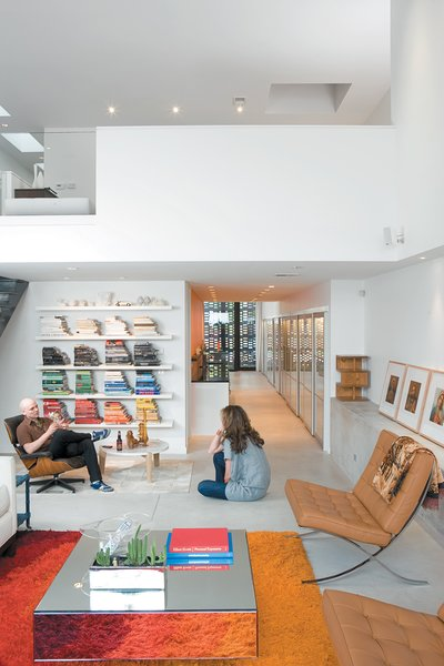 12 Lovely Little Lofts - Photo 3 of 12 - Hernandez and Surratt relax in their living room, which is enlivened by the house's internal topography. A short flight of steps divides the interconnected areas and offers a place to sit. Above is a loft that can be converted into a bedroom.