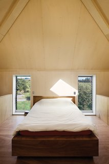 The mezzanine bedroom sits beneath the off-center apex of the pyramid roof, with a view over the orchard, one of McKenzie's few stipulations for the home's design.
