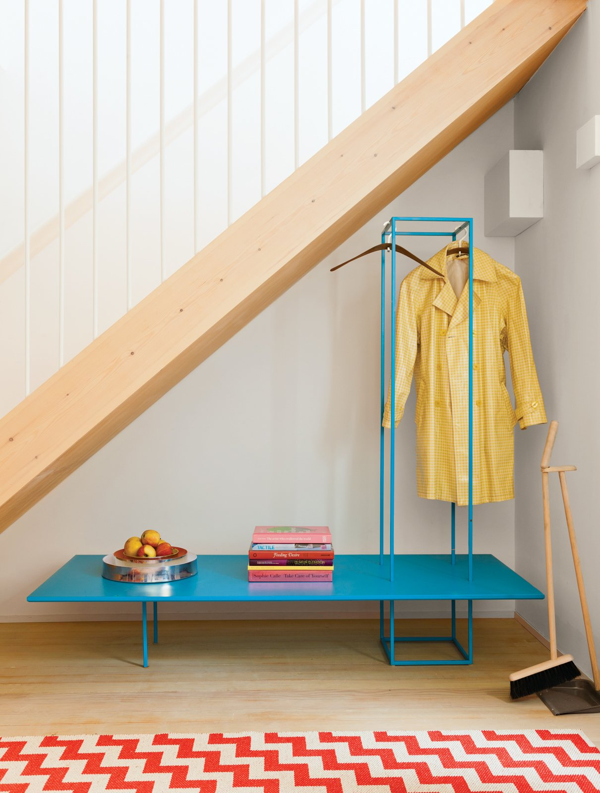 Furniture with emphasized linear elements helps prevent the appearance of clutter in small spaces. It's particularly effective when highlighted in playful colors like the blue bench storage rack in this London guesthouse. Photo by Ben Anders. Tagged: Staircase.  190+ Best Modern Staircase Ideas by Dwell from A Colorful, Custom-Built Guesthouse in London