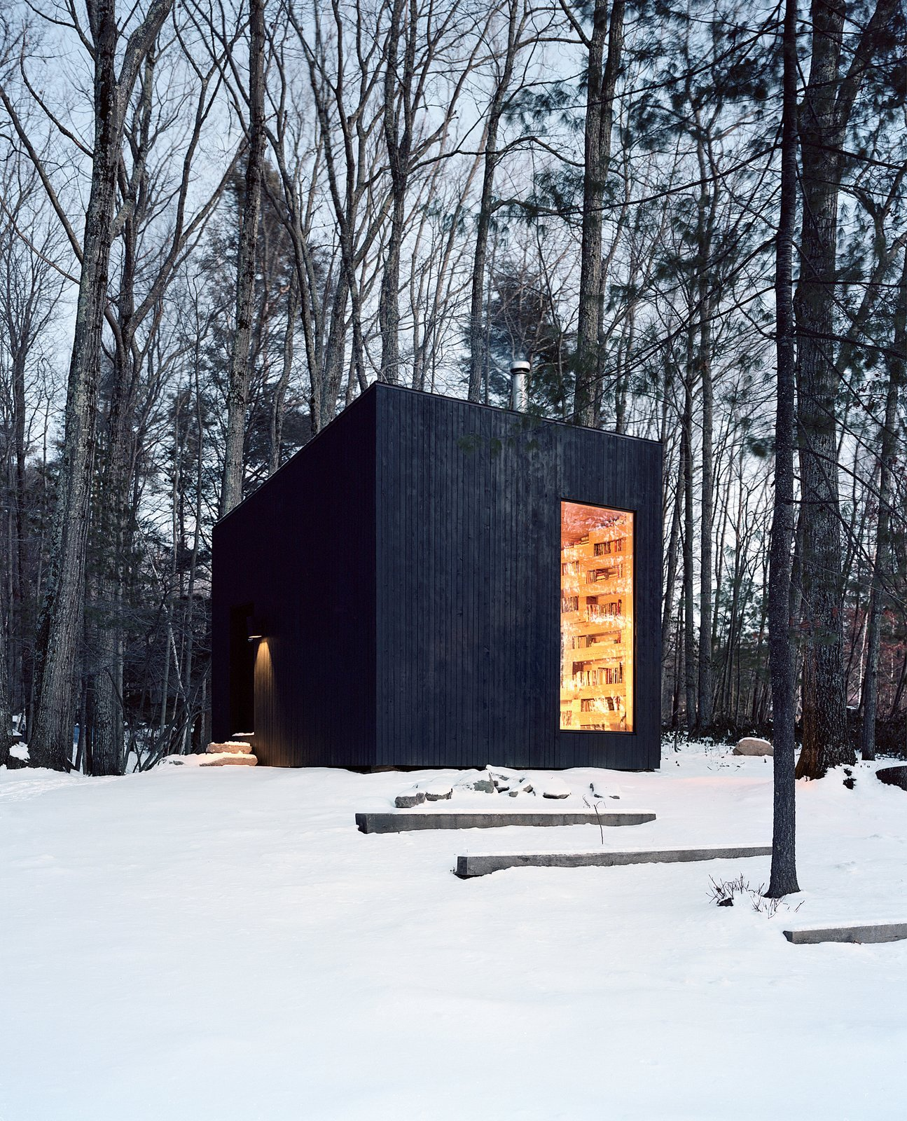 Jason and Suzanne Koxvold commissioned Studio Padron to design a 200-square-foot guesthouse on their Ellenville, New York, property. The geometric structure's dark cedar cladding contrasts with the inviting interior, which is heated by a cast-iron Jøtul stove. A layer of built-in bookshelves made from felled oak lumber also helps insulate the building in winter.