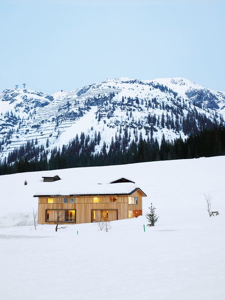 The Strolz House nestles in the winter snow at the edge of the Austrian village of Lech. Large wooden shutters help protect the windows against avalanche damage.