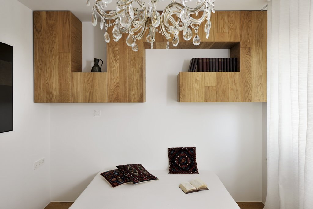 """The ceiling in the bedroom adorned with a crystal chandelier, which (along with the other vintage accessories) gives this residence a unique soul,"" Dragisic says.  Storage by Dwell from A Compact Minimalist Apartment in Slovenia"
