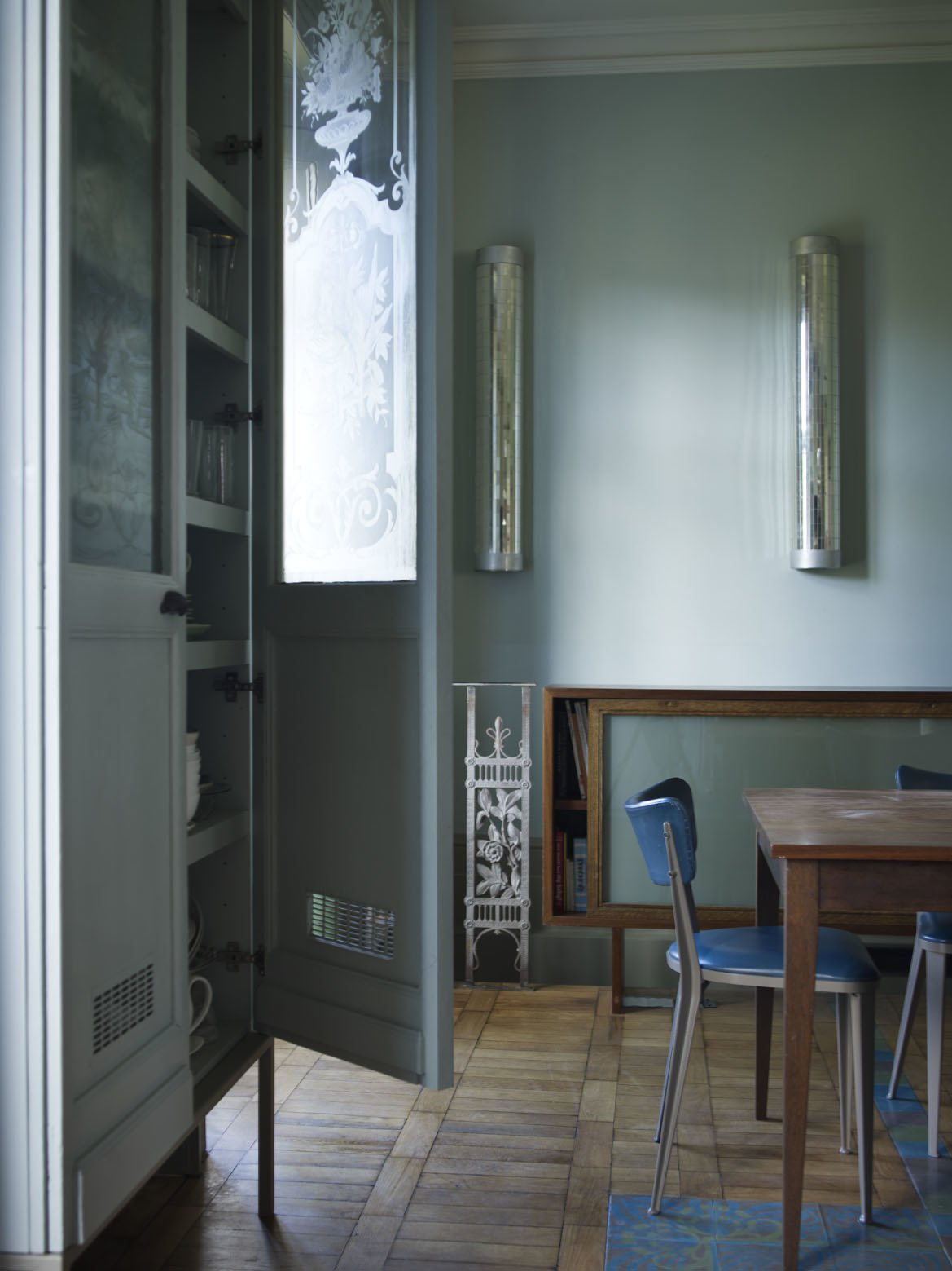 The bespoke sideboard (hiding the stairway to the basement) and the kitchen table were both built from wood sourced from a school science laboratory, while the sliding door that fronts the sideboard was salvaged from the National Museum of Scotland.  Photo 2 of 12 in A Gracious London Terrace House Is Reborn with Salvaged Materials