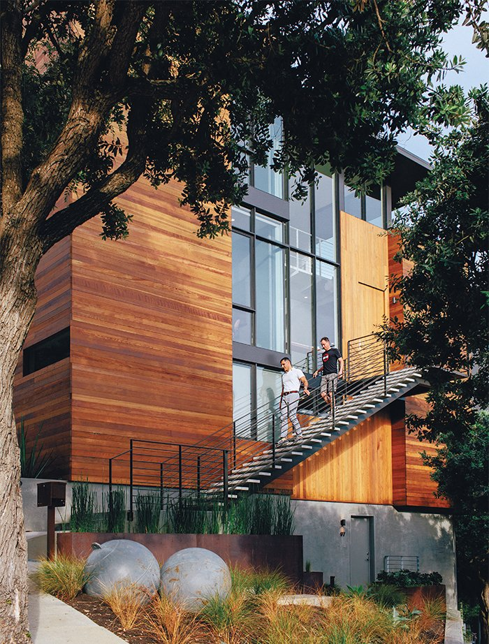 Baba and Bradley descend the staircase leading to the second-floor entrance, located above an in-law rental unit. The steel buoys are World War II era. Tagged: Exterior, House, and Wood Siding Material.  Photo 3 of 19 in A Home with Eclectic Style Looks Just Right