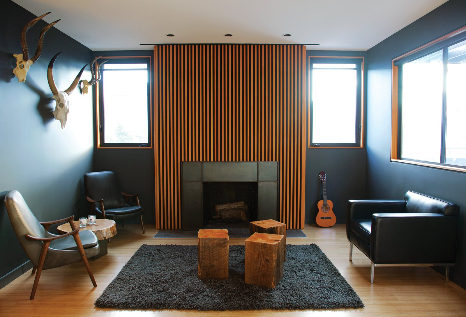 "LOS ANGELES HOME WITH WOOD-CLAD INTERIOR  Home owner Bill Thompson warmed up his otherwise dark living room with a series of Douglas fir slats was applied above the fireplace as well as other wood accents throughout the room.  A series of Douglas fir slats was applied above the fireplace. Tagged: Living Room, Wood Burning Fireplace, Standard Layout Fireplace, Chair, Rug Floor, Medium Hardwood Floor, and End Tables.  Photo 2 of 9 in You Won't Be Calling This House a ""Man Cave"""