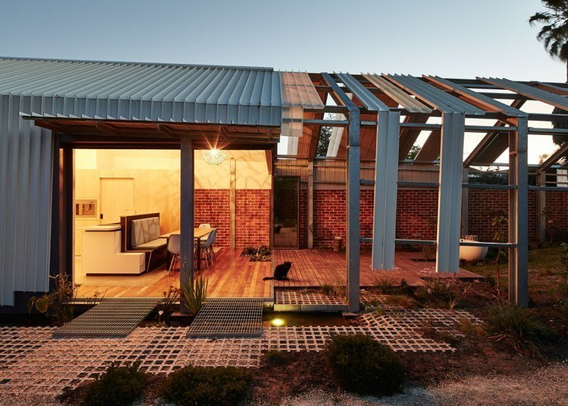 A steel-framed, bi-fold door system by Skyrange Engineering separates the edge of the house from the outdoor area.  Cut Cut Paw Paw by Allie Weiss from Bold Homes with Cutaway Walls