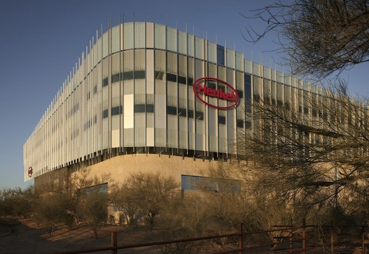 """Henkel North American Consumer Products Headquarters (Scottsdale, Arizona: 2010)  Building in the Sonoran desert doesn't immediately bring the word """"sustainable"""" to mind. This 348,000-square-foot Scottsdale office space for Henkel, a German consumer goods company, is a stylish rejoinder to that impression. Here, nature is put to work. The roof is covered in a 1.5-acre garden of native plants, with solar panels that power the building's banks of washers and dryers, a substantial green gesture for a company that makes laundry detergent. And the exterior, designed by CH2M Hill and Will Bruder + Partners, features custom glass etched in a pattern that reduces the intensity of the sunlight and a breathable skylight over the central atrium. Turning down the heat only seems fitting for the makers of a successful line of deodorants.   Photo by Henkel"""