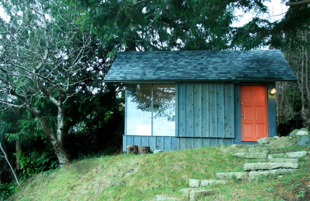 A recycled barndoor track and wheels affords privacy behind a siding covered panel.  Tiny Homes  by Erika Heet from Tiny Studio Cabin by Hinterland Design