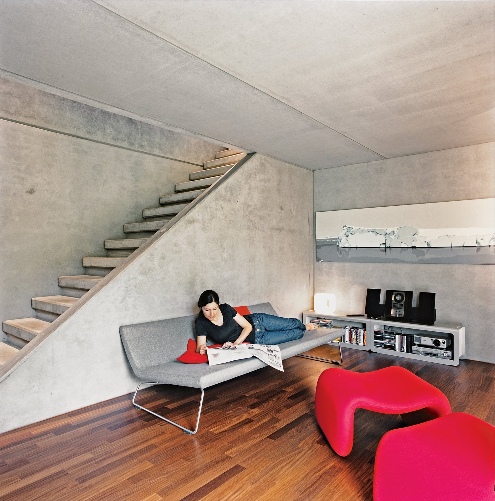 At the bottom of the stairs is a second living space that includes a fireplace. The couple couldn't find a television that didn't clutter the cool minmalism so they prefer to use a projector to watch movies. The sofa was designed by Barber-Osgerby for Cappellini, and the Djinn chair is by Olivier Morgue.  Photo 11 of 11 in Swiss Mix