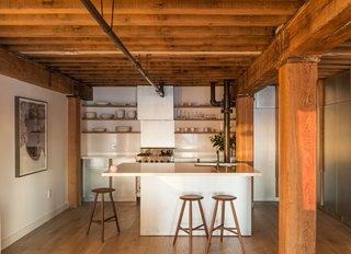 The custom zinc cabinets and quartzite countertops of Mark Berryman's Tribeca apartment reflect the sun as it sets over Manhattan. Workstead designer Robert Highsmith kept the apartment's original fir beams and painted its existing pipes Onyx by Benjamin Moore. The counter stools are by Sawkille, and the floors are white oak from LV Wood. The range is by Viking.