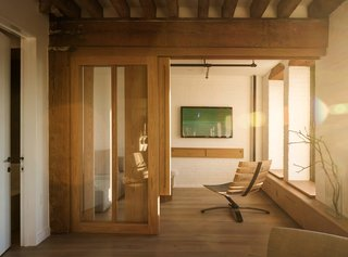 A custom white oak sliding door fabricated by Markus Bartenschlager opens to a guest room with a Bilge lounge chair by Uhuru.