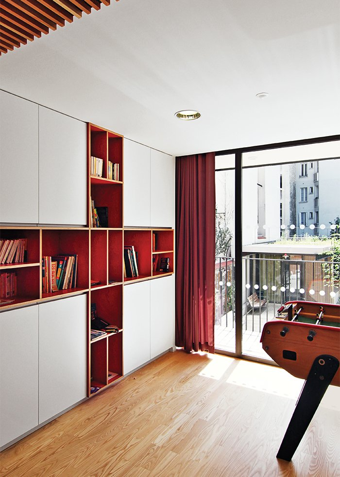 Brambilla designed and crafted the built-in bookcase in a common area from laminated red birch. Tagged: Storage Room and Shelves Storage Type.  Storage by Dwell from How California Style Influenced a Group Home in Paris