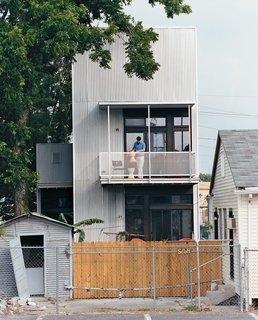 New Orleans, LA - Photo 10 of 11 - Resident Tony Vanky gets the second-story deck prepared for guests. The grittiness of the Black Pearl neighborhood is plainly visible.