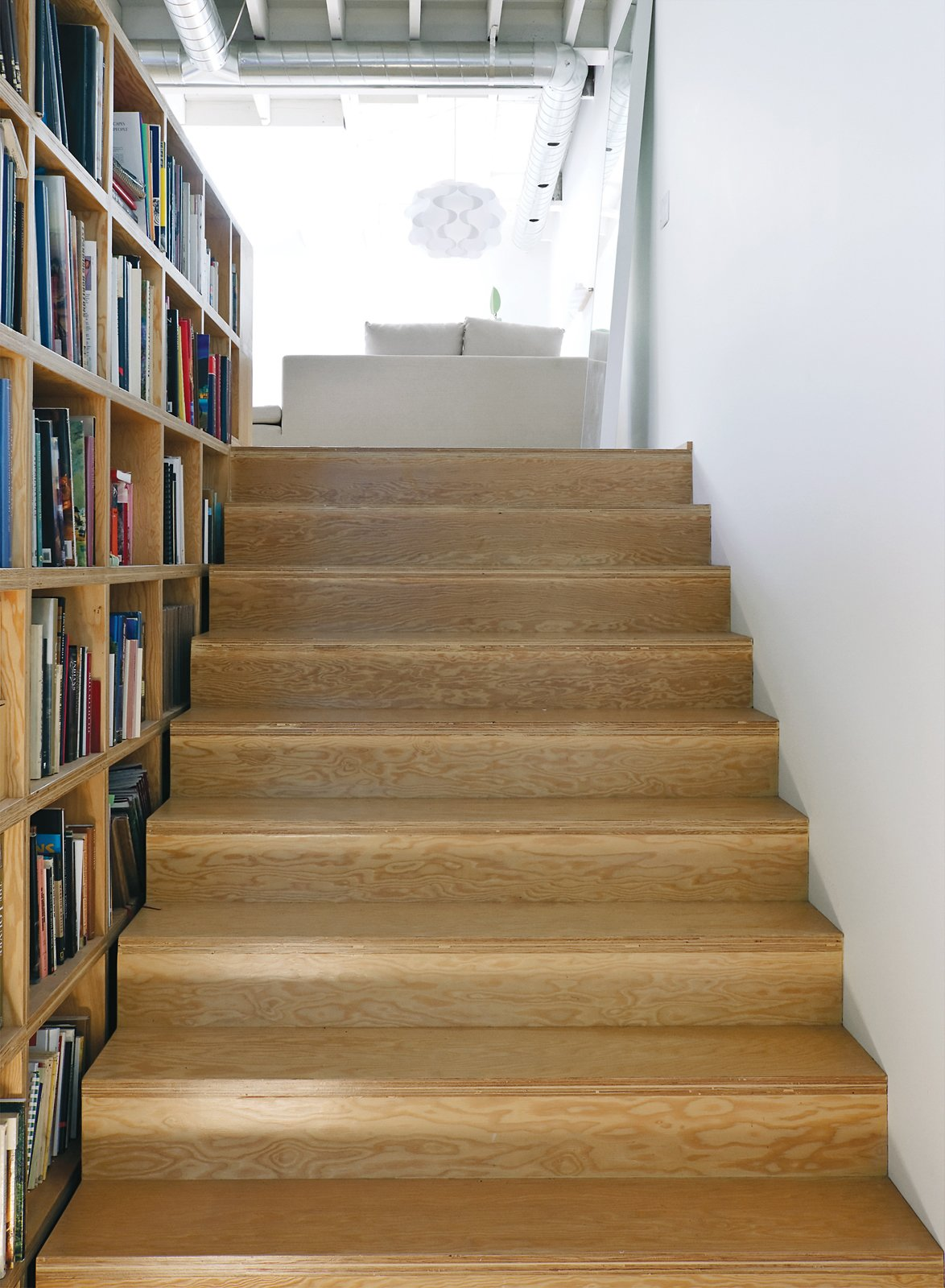 The adjacent extra-wide stairs provide easily accessible storage space; the custom bookcases, made of the same Douglas fir plywood as the treads, follow the rise of the steps to the bedroom.  Photo 8 of 9 in An Art Studio That Would Make Picasso Jealous