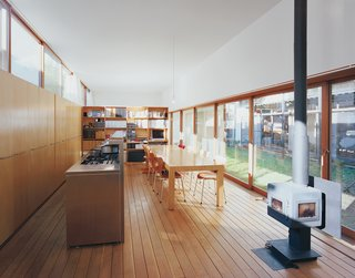 The architects designed the large dining table, which is framed by the open kitchen, the wood-burning stove, and the garden beyond.