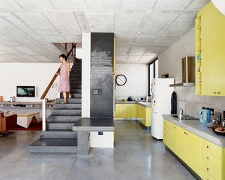 Katz's Cradle - Photo 4 of 10 - The freestanding staircase was built three times before Gregory deemed it structurally sound—a tribute to the architect's tenacity. The high-tech end result was achieved using small custom-made plastic reinforcing fibers. The galley-style kitchen with its bold use of color was Caryn's choice. She fell in love with the name of a paint swatch called Canary Yellow and then left it to Gregory to fine-tune the exact hue.