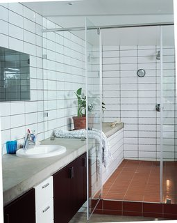 Katz's Cradle - Photo 7 of 10 - The shower-and-bath-in-one allows for the open feel of the house to translate within the bathroom. Simple concrete slabs function as countertops with inexpensive tiles laid floor to ceiling.
