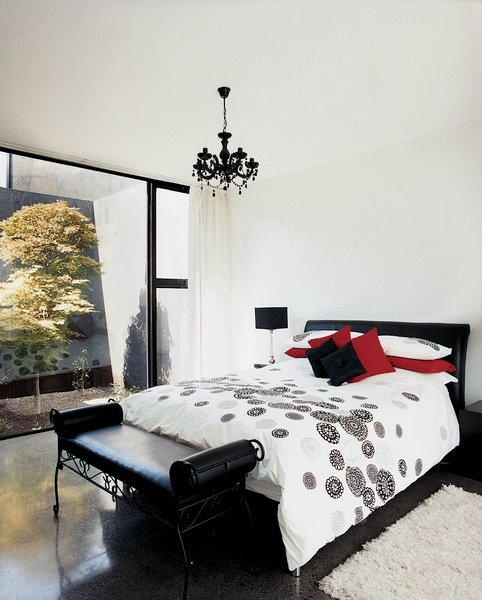 The decor of the master bedroom remains stark, but a black chandelier brings a touch <br><br>of complexity to an otherwise white space. The same maple tree can be seen through the rear glass wall, providing a visual focus for this wing of the house.