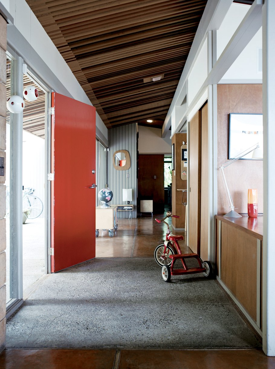 The Pfeiffers' furnishings tend to be of two stripes: flea-market treasures or prototypes and castoffs of Eric's design process. The low tables behind the front door are of Eric's design. Tagged: Hallway and Concrete Floor.  Photo 2 of 9 in Oakland Aesthetics
