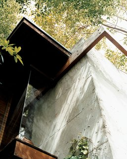 Ray Kappe-Designed Multilevel House in Los Angeles - Photo 10 of 12 - This detail shows the conjunction of concrete with wooden beams, where flush glass windows angle outward to the canopies of nearby trees. The detail also encapsulates Ray's vision for the house: a synthesis of the rational and the intuitive.