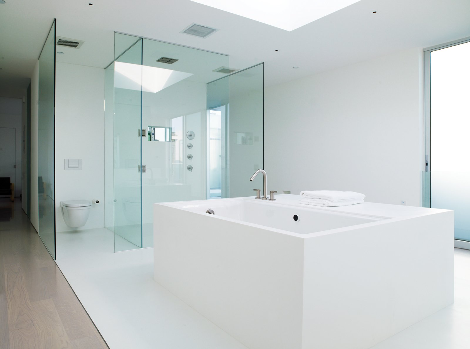 In the master bathroom, an oversize tub is graced with a generous skylight above it.