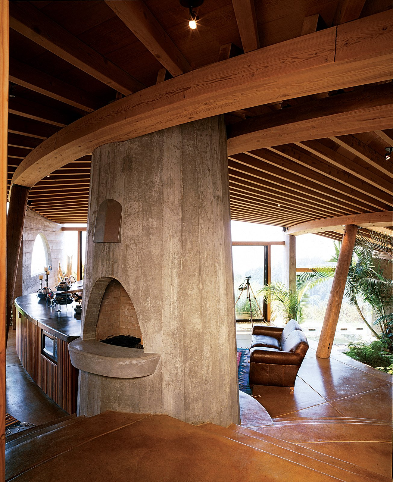 The interiors of many of Muennig's houses emphasize natural building materials such   as wood, concrete, and stone. Plant life and nature are intrinsic to the Pfeiffer Ridge House IV. Tagged: Living Room, Wood Burning Fireplace, and Sofa.  Photo 1 of 9 in Big Sur: Coastal Commissions