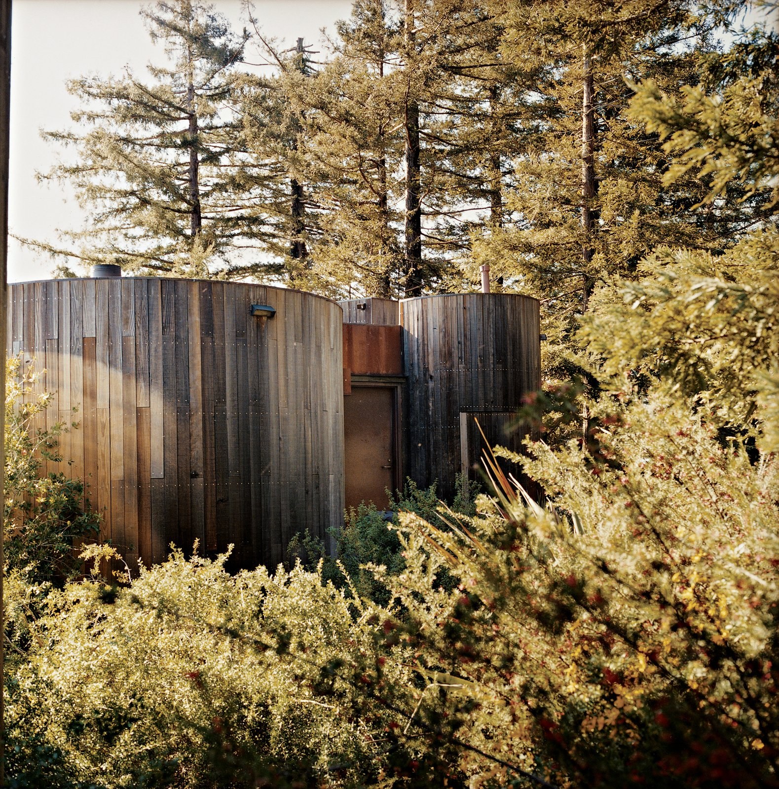For the Butterfly cabin, which is part of the Post Ranch Inn, Muennig chose materials that age gracefully when exposed to the elements. He regularly uses Cor-Ten steel, a group of steel alloys that form a stable rust-like appearance when battered by wind and rain. Tagged: Exterior, Cabin Building Type, Wood Siding Material, Metal Siding Material, and Flat RoofLine.  Photo 72 of 101 in 101 Best Modern Cabins from Big Sur: Coastal Commissions