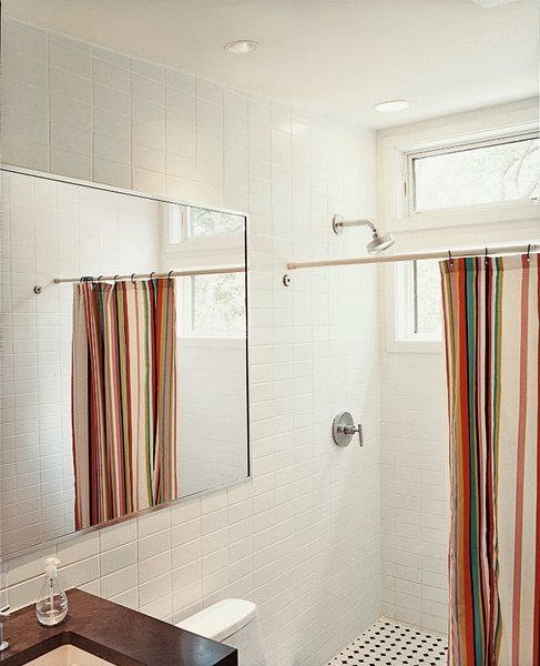 A brightly striped shower curtain lends bright punctuation to an otherwise austere bathroom.