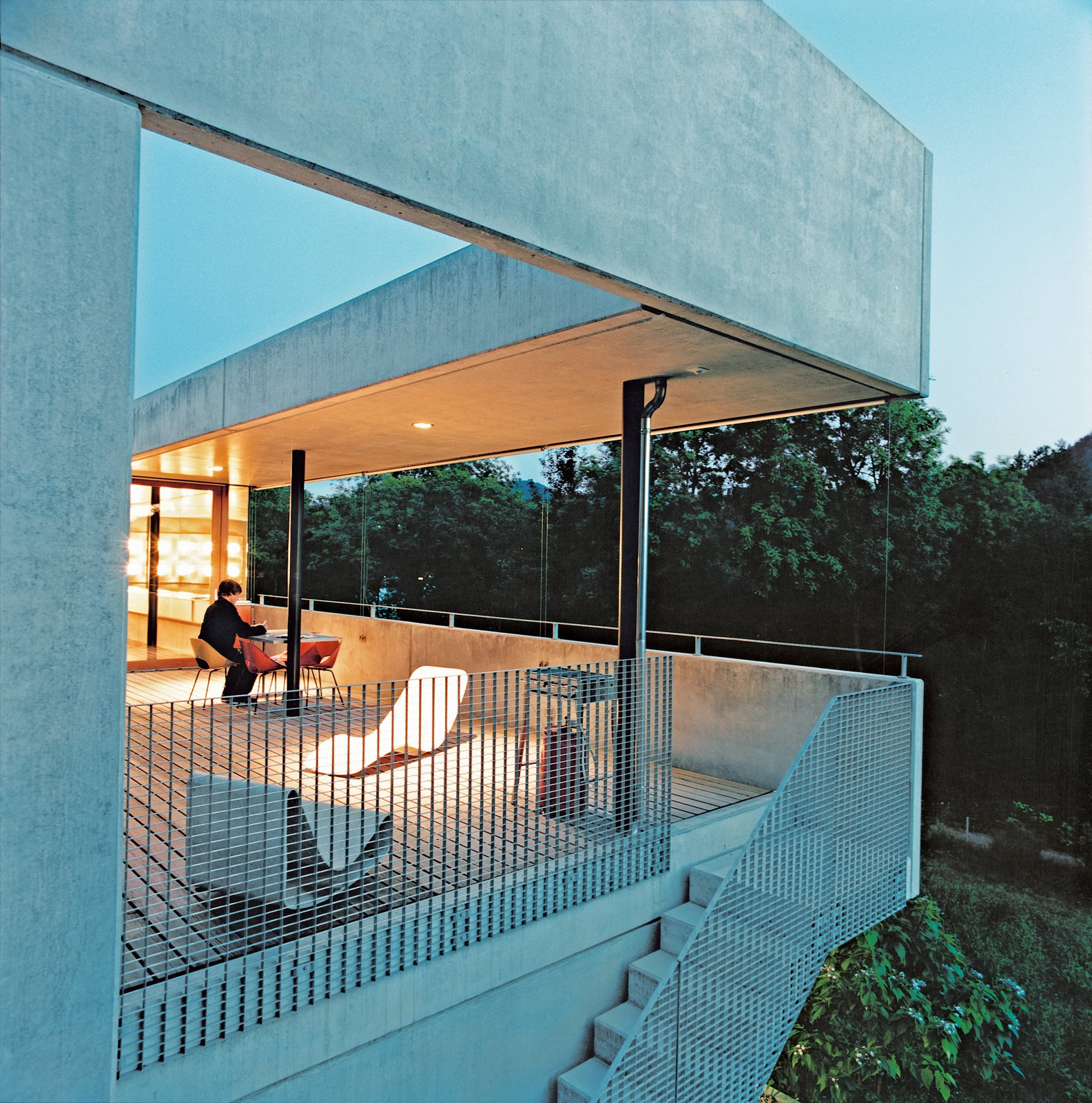The couple do their outdoor lolling on Willy Guhl's concrete Loop chair (near grating) and Superieur's Divan lounge (near the table), both Swiss products. Tagged: Outdoor, Wood Patio, Porch, Deck, and Large Patio, Porch, Deck.  Photo 4 of 11 in Swiss Mix