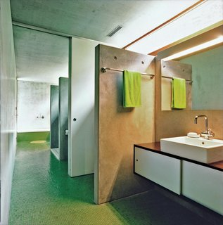 The bathroom is a long, linear space with a letterbox window to provide natural light. There are two toilets, a pair of sinks, and two showers.