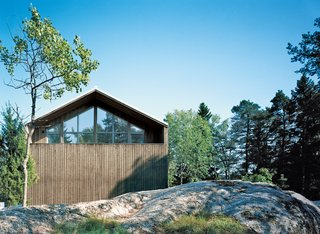 The pitched facade has a sculptural play of spruce siding and triple-glazed windows that reflect the surrounding treetops.