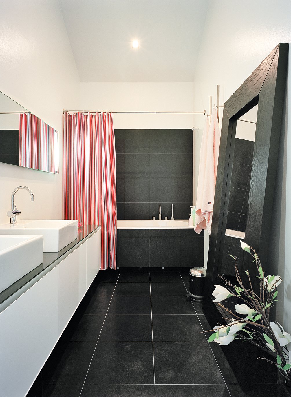 The master bathroom is one of few spaces that lacks windows, but it opens onto the brilliantly daylit master bedroom. Tagged: Bath Room, Vessel Sink, Ceiling Lighting, Ceramic Tile Floor, Alcove Tub, and Drop In Tub.  Photo 11 of 13 in Sum of Its Parts