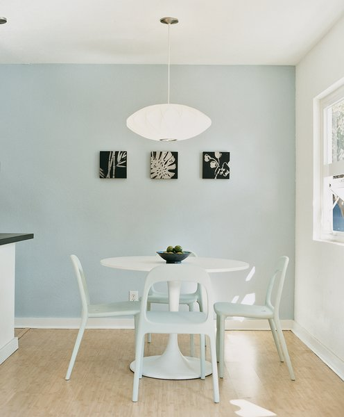 Due to the tight budget, the fixtures and furnishings had to be a mix of high and low. Instead of a Saarinen Tulip table for the dining room, they found a similar style with matching chairs from Ikea, then hung a George Nelson lamp overhead.