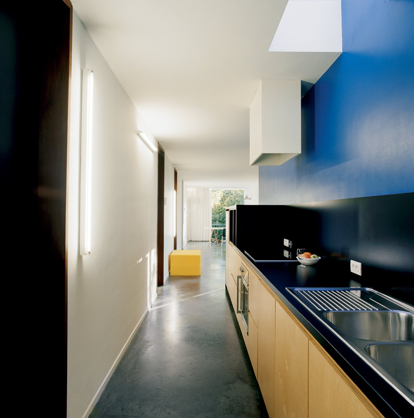 "The kitchen is a vibrant deep blue. ""It's the same color Le Corbusier used in the corridor of his Villa Savoye in Poissy,"" Van Everbroeck reports. Tagged: Kitchen, Wood Cabinet, and Concrete Floor.  Best Photos from The Tree of Ghent"