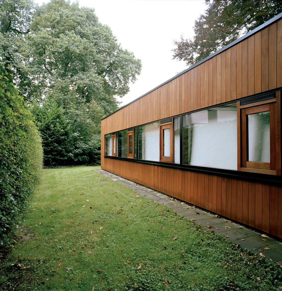 Only the rear of the house suggests the building's earlier incarnation as a 1960s bungalow, and even here the original brickwork is obscured by wood cladding. Tagged: Exterior, Wood Siding Material, and House. Best Photos