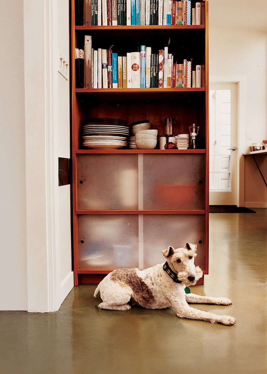 Sparky the wirehaired fox terrier takes a load off in front of one of the cherry-ply cabinets with sanded acrylic doors that Azevedo built for the kitchen. Tagged: Storage Room and Shelves Storage Type.  Photo 3 of 9 in Bay Wash